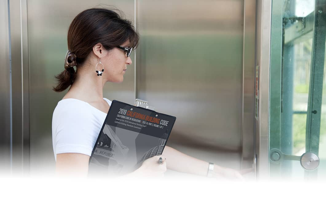 A woman pressing an elevator button holding an inspection book.